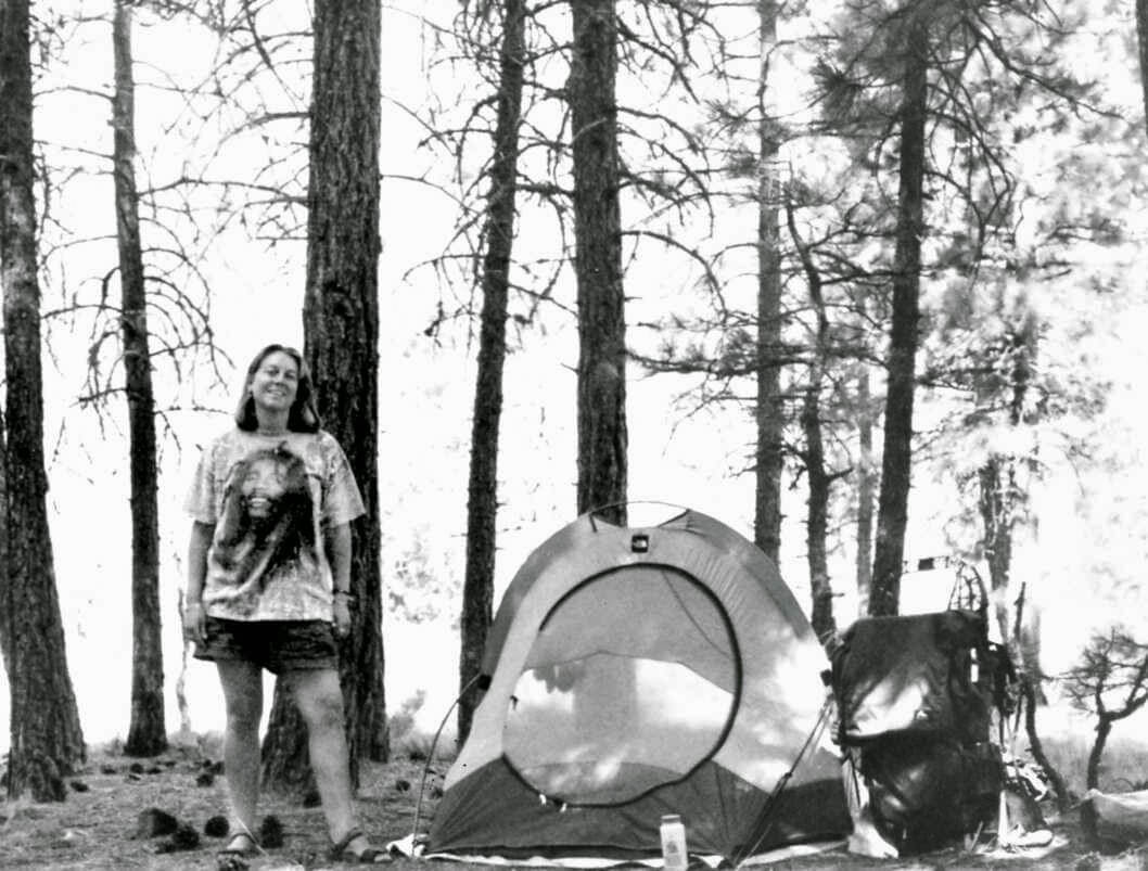 Photo of Cheryl Strayed in a forest, standing by a tent