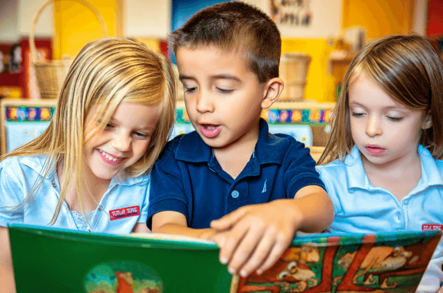 Three children read a picture book together