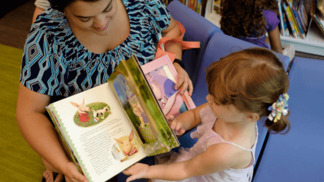 Adult reads a book to a young child