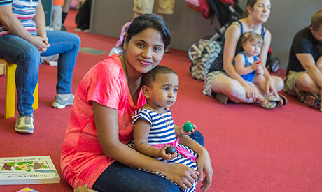 A woman and toddler look at the camera while taking part in a Storytime circle