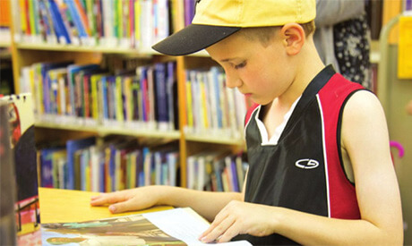 Young boy in a baseball cap reads a book