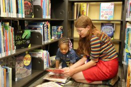 A young woman reads with a little girl in the library.