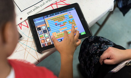 A young child uses a tablet to play a game