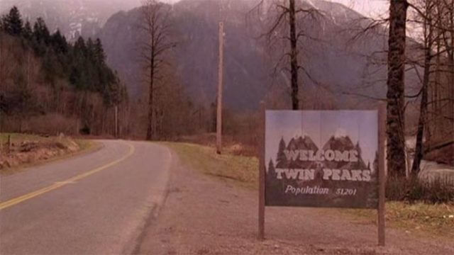 """A sign on an abandoned road reads """"Twin Peaks, Population 5,1201"""""""