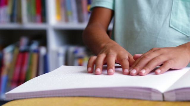 Close up of a child's hands reading a braille book