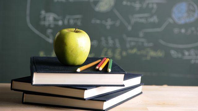 A green apple sitting on top of a stack of books in front of a chalk board