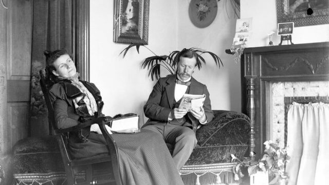 A black and white photo of a couple sitting in a parlor