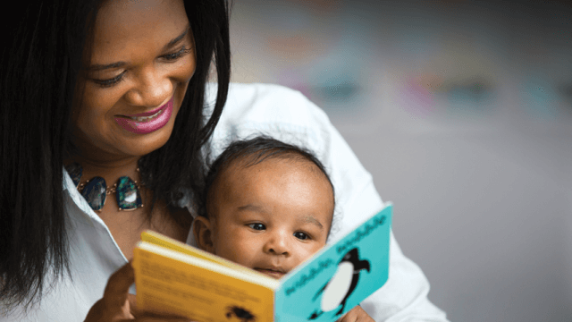 mother reading a board book to a young baby