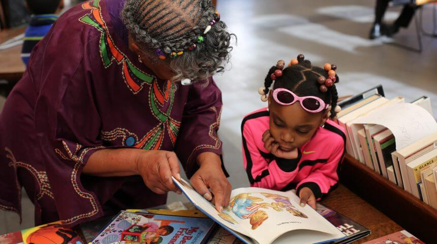 Women looks at a book with a young girl