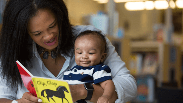 Baby and caregiver read the book, Clip Clop.