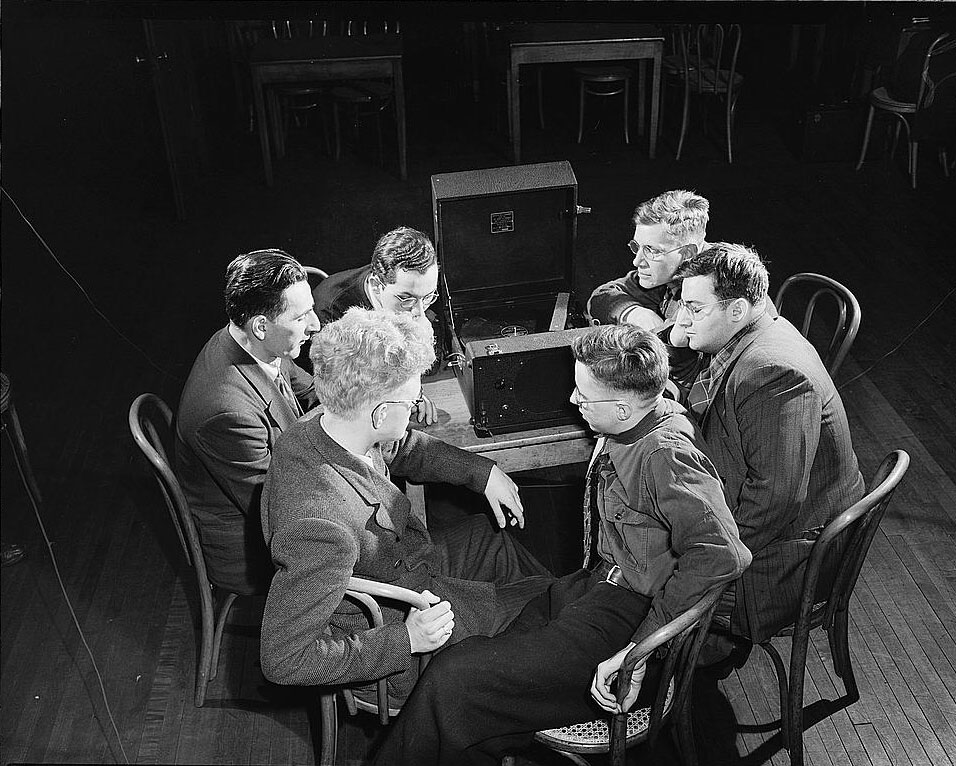 A group gathered around an old NLS Talking Book Rigid Disc player listening