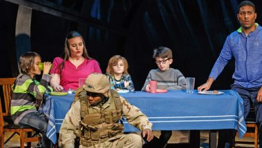 """Soldiers crouch in front of a dinner table in the opera """"The Long Walk."""""""