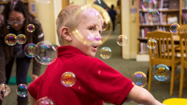 A child playing with bubbles in the children's room at CLP