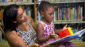 Child sits in parent's lap while parent reads book to child