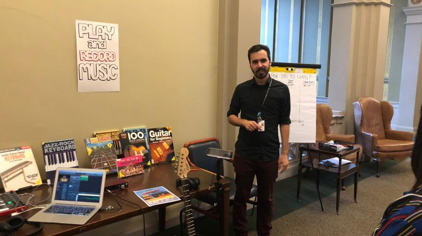 "Photo of the Library's music station. A staff member stands next to a table with a sign that reads ""Play and record music."" The table includes books, a laptop, and an electric guitar. Behind the staff member is a sign that asks ""How did you learn?"""