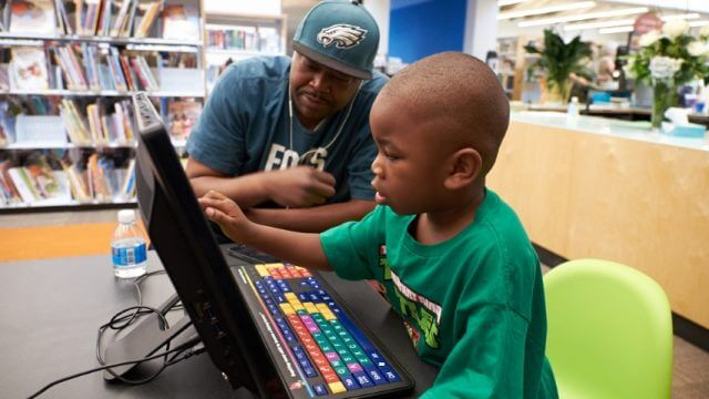 An image of a father observing his son using one of the Library's computers.
