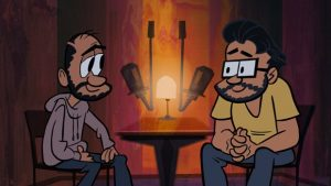 Two bearded men speaking at a table with two microphones.