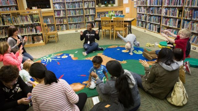 Librarian leads children and caregivers in storytime