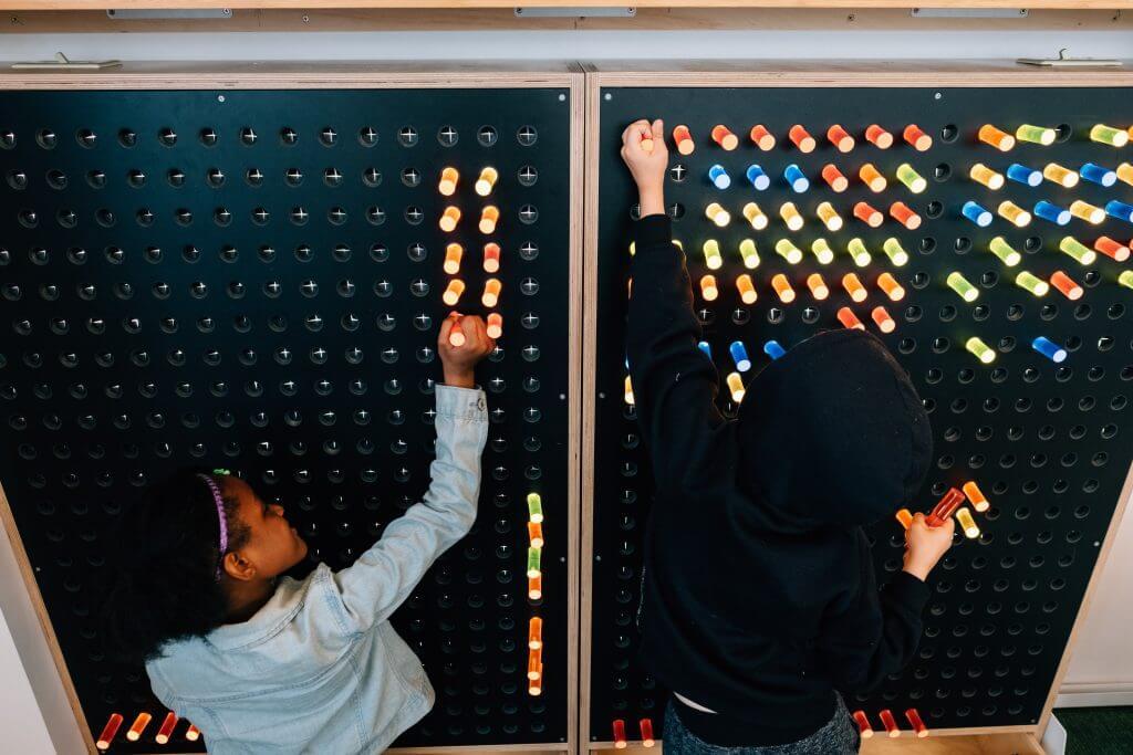 Children explore a life-sized light wall.