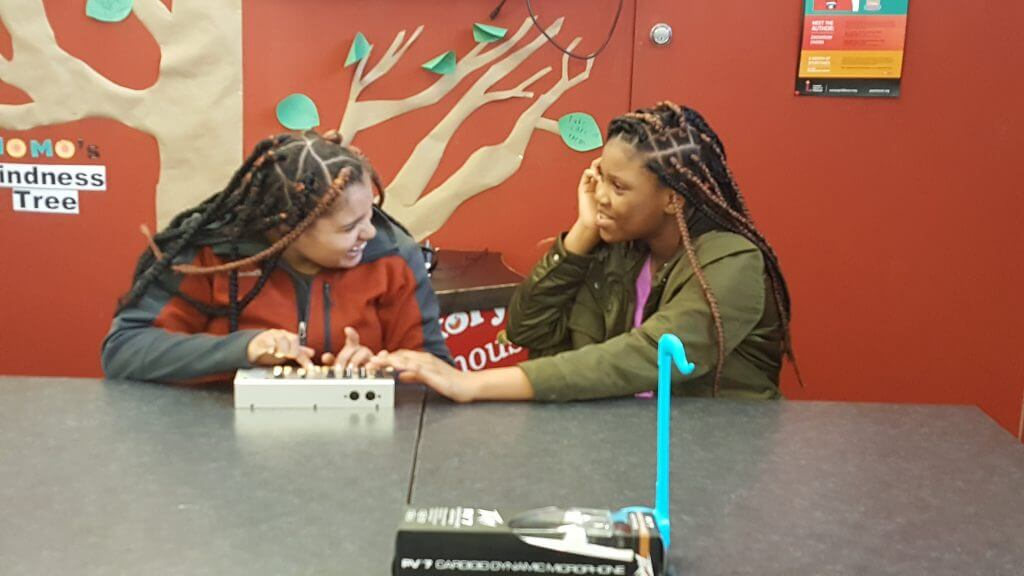 Image of two teen girls laughing while playing a game.