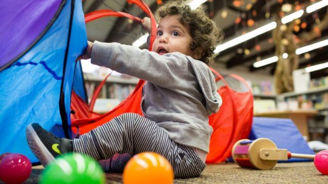 Image of a young child playing with a tunnel tube at Family Playshop.