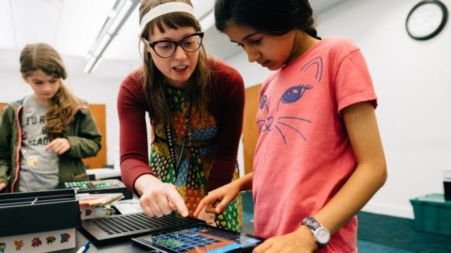 Librarian helps two tweens use tablets to play games and code