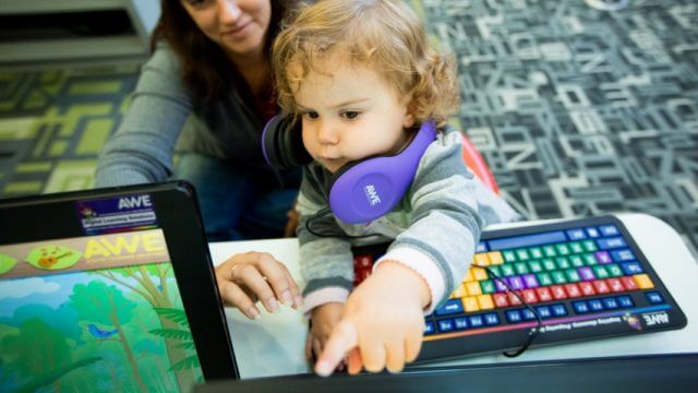 A parent helps their child at a computer/awe station