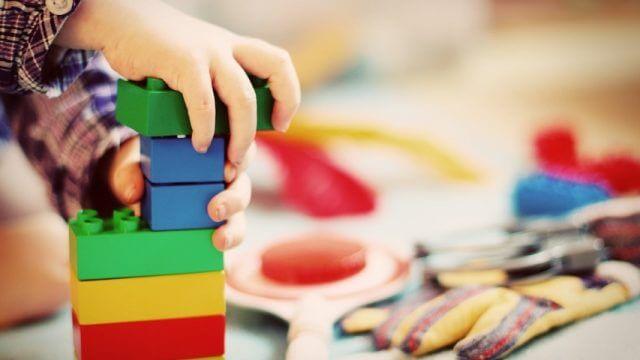 A child stacks blocks together