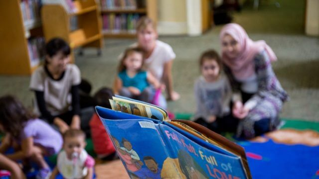 A book is read to several children and their caregivers