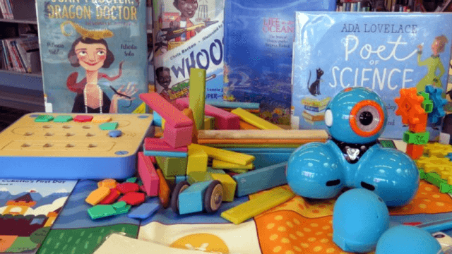 Four books, several robots, and a puzzle sit on a table