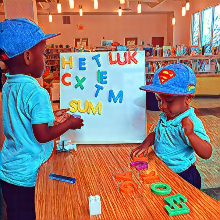 Two children explore magnetic letters at the Library.