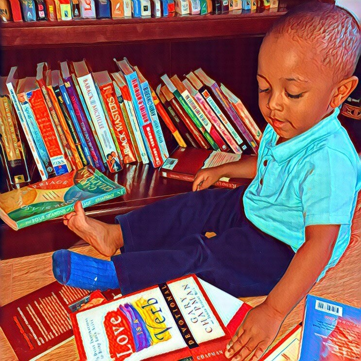 A young boy explores a stack of books pulled from a shelf.