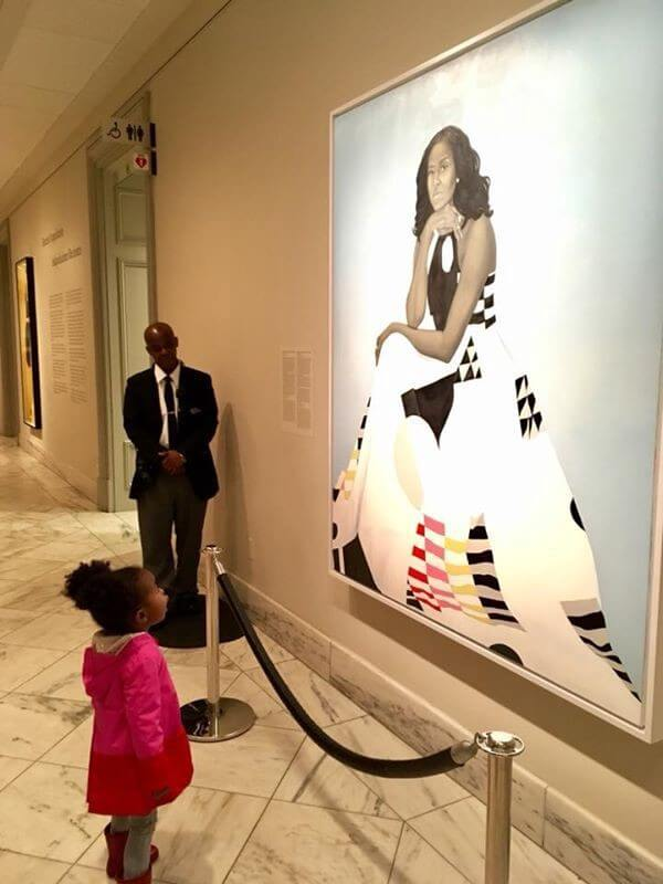 Young girl viewing a portrait of Michelle Obama in a museum.