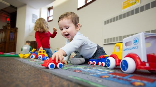 Two children play with cars and trucks