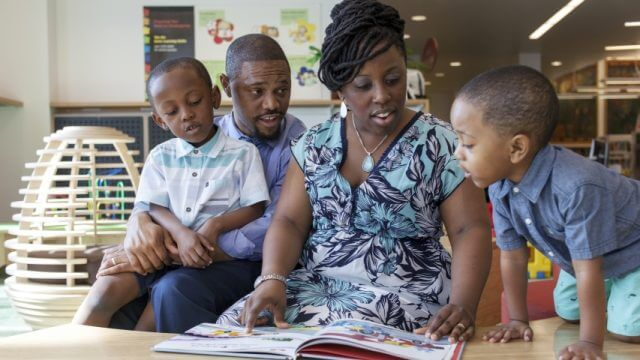 Two parents and two children read a book together
