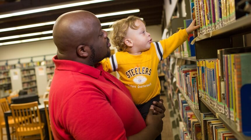 A parent holds their child in their arms while the child looks at books