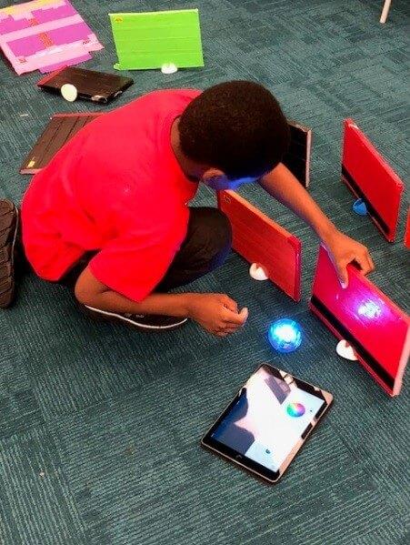 A child explores the Sphero robot.
