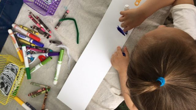 A child colors with markers and crayons on a long piece of paper