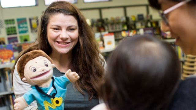 Librarian uses puppet for caregiver and child