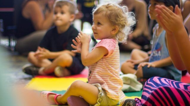 Toddler girl smiling and clapping at library storytime
