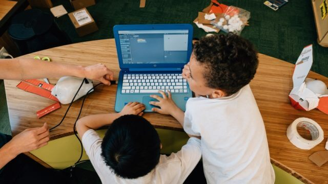 Two young children use a laptop computer together