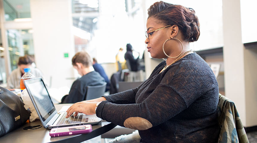 Woman typing on a laptop in a library.