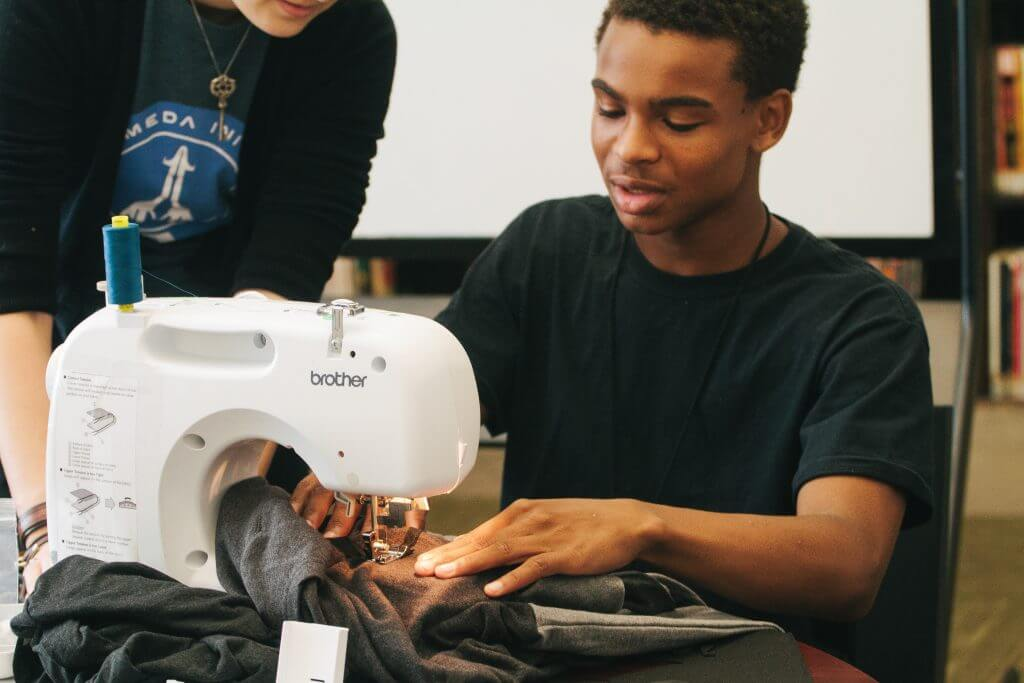 A teen uses a sewing machine during a library program.