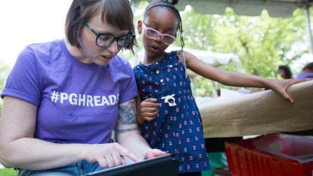 A librarian showing a child something on a tablet at the 2018 Summer Reading Extravaganza