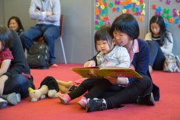 An adult and child read together before storytime.
