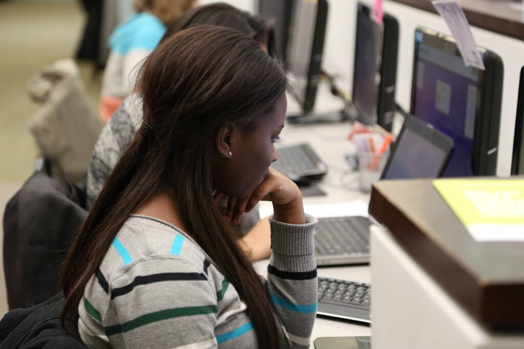 A teen uses a library computer.