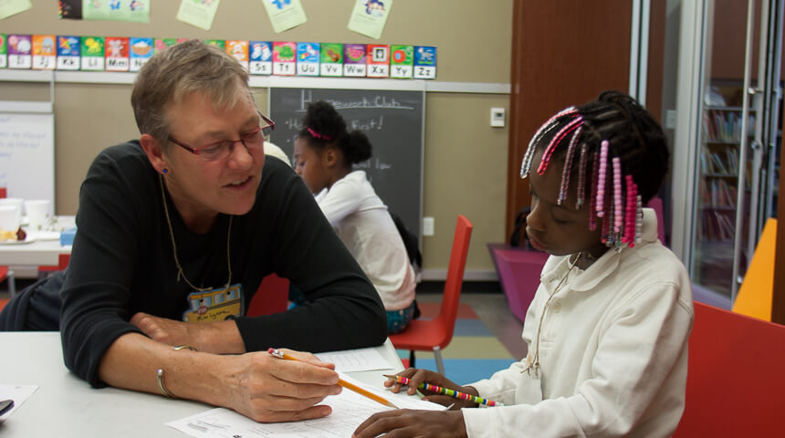 A volunteer helps a child with homework
