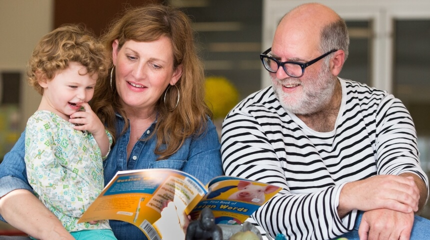 Parents read with their child at the library