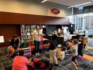 Children dance with scarves during a storytime.