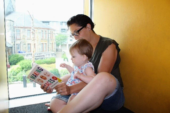 A parent and child read a book together in a window seat at CLP - Squirrel Hill.